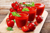 Glasses of tomato juice on wooden table, closeup — Stock Photo