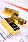Gold bullion on documents background — Stock Photo
