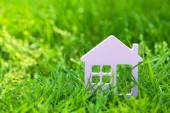 Small model of house over green grass background — Stock Photo