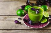 Glass of green healthy juice with basil and limes on table close up — Stock Photo