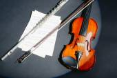 Violin and flute with music notes on dark background — Stock Photo