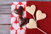 Chocolate heart shaped candies on sticks on red napkin, closeup — Stock Photo