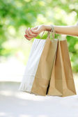 Female hand holding shopping bags outdoors — Stock Photo