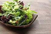 Ahşap masa üzerinde taze karışık yeşil salata tabak kapat — Stok fotoğraf