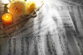 Beautiful roses with pearls and candle on music sheets background — Stock Photo