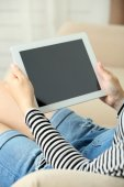 Female hand holding PC tablet on home interior background — Stock Photo