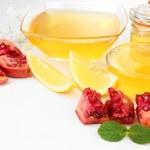 Sweet honey with pomegranate and lemon isolated on white — Stock Photo #78066998