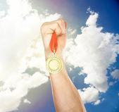 Goldene Medaille in der Hand am Himmel Hintergrund — Stockfoto