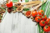 Tomatoes, wooden spoons with fresh herbs and spices on wooden background — Stock Photo