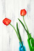 Beautiful red tulips in vases on wooden background — Stock Photo