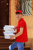 Delivery boy with cardboard pizza box near house of customer, outdoors — Stock Photo
