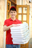 Young man delivering pizza box near house — Stock Photo