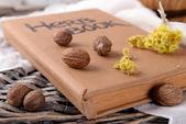 Sušené byliny s muškátovým oříškem a kniha na stole zblízka — Stock fotografie