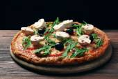 Tasty pizza with vegetables and arugula on black background — Stock Photo