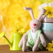 Easter bunny with painted Easter eggs with flowers on wooden table on yellow  background — Stock Photo #78083074