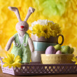 Easter bunny with painted Easter eggs with flowers on wooden table on yellow  background — Stock Photo #78083076