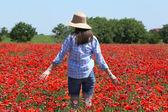 蓝蓝的天空背景上罂粟领域走过的女人 — 图库照片