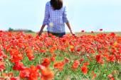 Woman walking on poppy field over blue sky background — Stock Photo