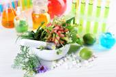 Herbs in mortar, test tubes and pills,  on table, on light background — Stock Photo