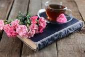 Old book with beautiful flowers and cup of tea on wooden table close up — Stock Photo