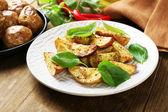 Pommes de terre cuites au four avec des feuilles de basilic en plaque blanche sur table en bois, gros plan — Photo