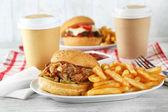 Leckere Burger und Pommes frites auf Platte auf Holztisch Hintergrund. ungesunde Lebensmittel-Konzept — Stockfoto
