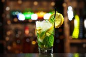 Glass of cocktail in bar on bright blurred background — Stock Photo