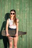 Girl with tattooed body, holding skateboard — Stock Photo