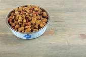Dog food in bowl on wooden table — Stock Photo
