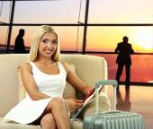Business woman with suitcase in hall of airport — Stock Photo