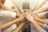 United hands of business team on workspace background top view — Stock Photo