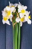 Beautiful bouquet of daffodils on wooden background — Stock Photo