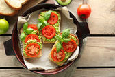 Vegan sandwich with avocado and vegetables on pan, on wooden background — Stock Photo