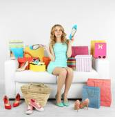 Woman with shopping bags and shoes on sofa in room — Stock Photo