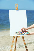 Female hand holding palette with paints and easel with canvas on beach — Stock Photo
