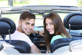 Young pretty couple in cabriolet, outdoors — Stock Photo