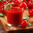 Glass of tomato juice on wooden table, closeup — Stock Photo #78883108