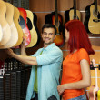 Beautiful young couple in music store — Stock Photo #78885674