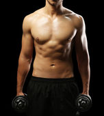 Muscle young man holding dumbbells — Stock Photo