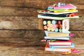 Stack of books and stationery on wooden background — Stock Photo