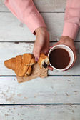 Female hands holding cup of coffee and cookies on wooden table close up — Stock Photo