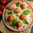 Meat balls in tomato sauce with boiled rice and lentil, wooden spoon on wooden background — Stock Photo #79068914