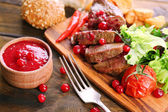 Beef with cranberry sauce, roasted potato slices on cutting board, on wooden background — Stock Photo