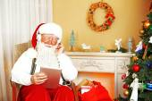 Santa Claus sitting with Digital tablet in comfortable chair near fireplace at home — Stock Photo
