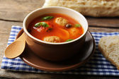 Tomato soup with meat balls on wooden spoon on wooden background — Stock Photo