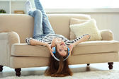 Woman listening music in headphones while lying on sofa in room — Stock Photo