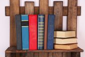 Wooden shelf with books on wall, closeup — Stock Photo