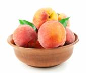 Ripe peaches in bowl isolated on white — Stock Photo