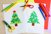 Creative paper Christmas tree on white paper sheet, scissors and colorful crayons on color table background — Stock Photo