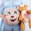 Beautiful young pregnant with baby toy  and picture on her belly, on light background — Stock Photo #79435952
